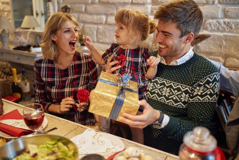 La familia feliz con los regalos celebra días de fiesta de la Navidad foto de archivo