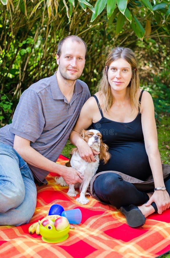 La familia feliz con su perro y el motherin embarazada parquean foto de archivo libre de regalías