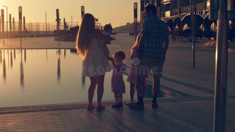 La familia feliz con tres niños que admiraban la puesta del sol reflejó en la superficie de la piscina imagen de archivo