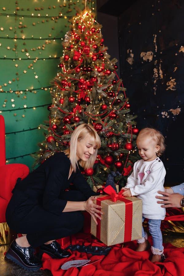 La familia feliz con un niño celebra el Año Nuevo cerca del árbol de navidad foto de archivo