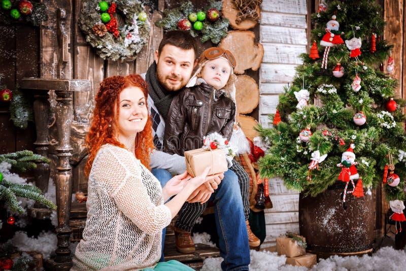 La familia feliz de la Navidad de personas del tres y de árbol de abeto con invierno del Año Nuevo de las cajas de regalo adornó  fotos de archivo