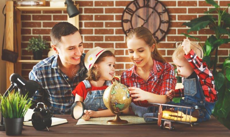 La familia feliz de madre, el padre y los niños se preparan para viajar t fotografía de archivo