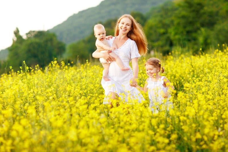 La familia feliz de madre y los niños corren en el prado del amarillo fotografía de archivo