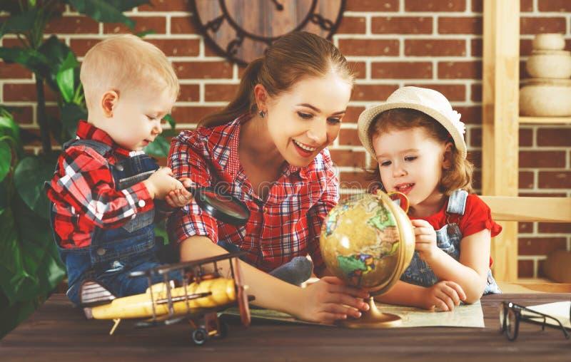 La familia feliz de madre y los niños se preparan para viajar viaje, pasto imagen de archivo libre de regalías
