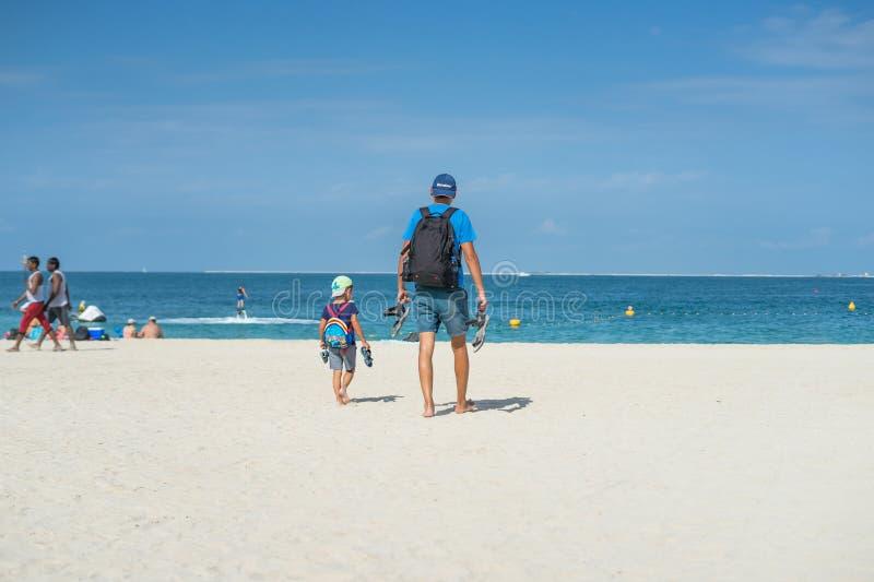 La familia feliz de padre, de madre y de hijo va las vacaciones en una playa tropical de la arena en verano Camellos en una playa foto de archivo libre de regalías
