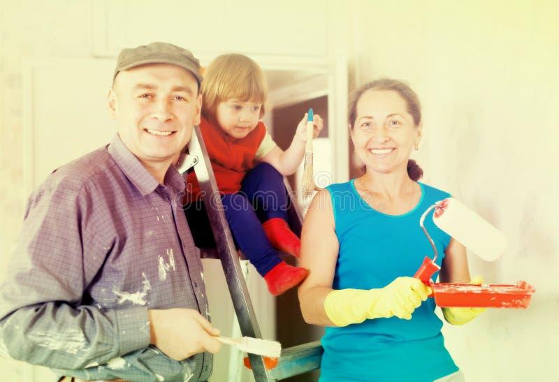 La familia feliz de tres repara fotos de archivo