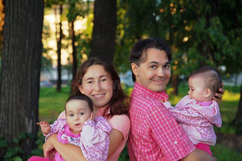 La familia feliz en el parque con el padre, la madre y el niño hermana b imagenes de archivo
