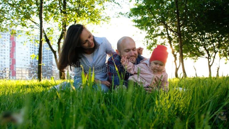 La familia feliz está descansando sobre la naturaleza Los padres juegan con una pequeña hija en un parque en el verano en la pues foto de archivo