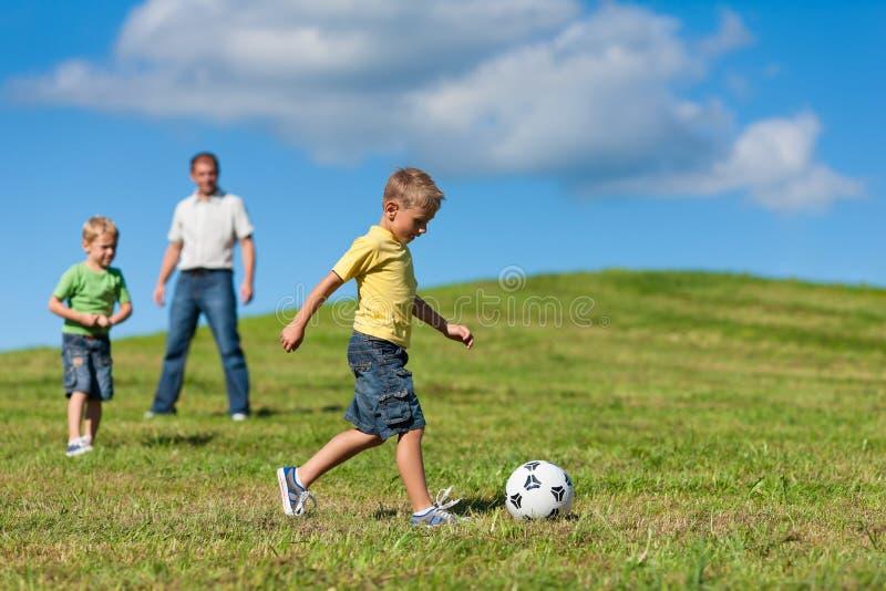 La familia feliz está jugando a fútbol en verano imagen de archivo