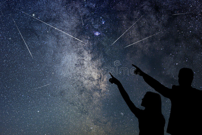 La familia feliz está mirando la lluvia de meteoritos Cerca cielo imagenes de archivo
