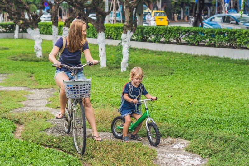 La familia feliz está montando las bicis al aire libre y la sonrisa Mamá en una bici fotografía de archivo libre de regalías