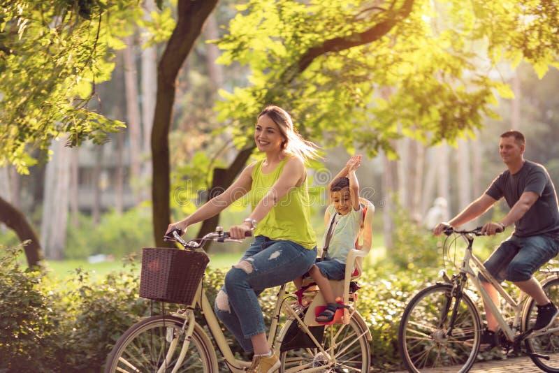 La familia feliz está montando las bicis al aire libre y al muchacho sonriente en la bici w fotos de archivo