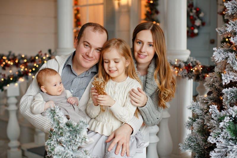 La familia feliz hermosa con la niña en suéteres hechos punto es fotografía de archivo libre de regalías