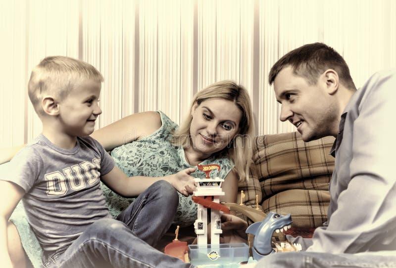 La familia feliz joven con el niño está descansando en casa sobre el sofá fotografía de archivo