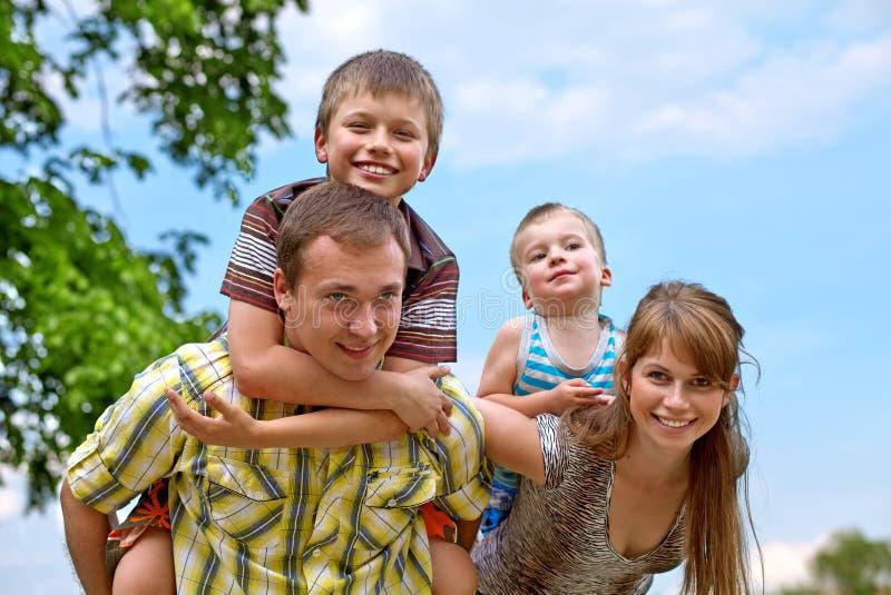 La familia feliz joven que da a dos hijos lleva a cuestas paseos imagen de archivo libre de regalías