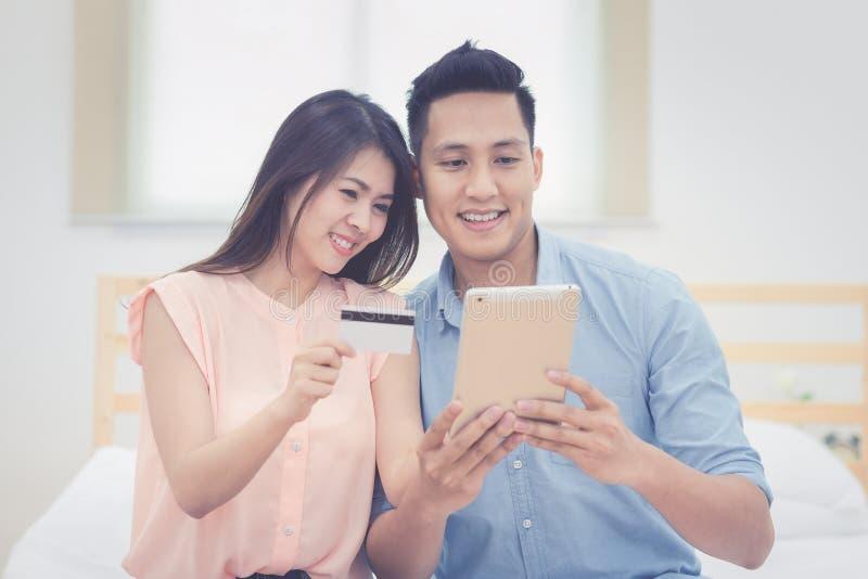 La familia feliz, los amantes asiáticos de los pares goza el usar de la tableta elegante fotografía de archivo