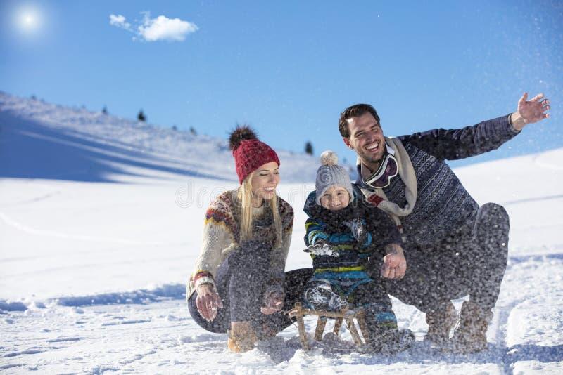 La familia feliz monta el trineo en la madera del invierno, entretenimientos alegres del invierno fotos de archivo