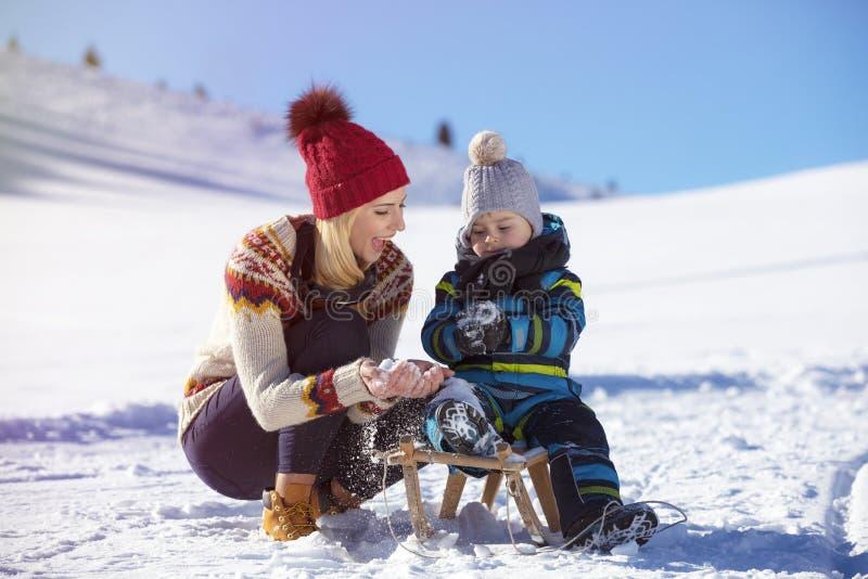 La familia feliz monta el trineo en la madera del invierno, entretenimientos alegres del invierno imagen de archivo