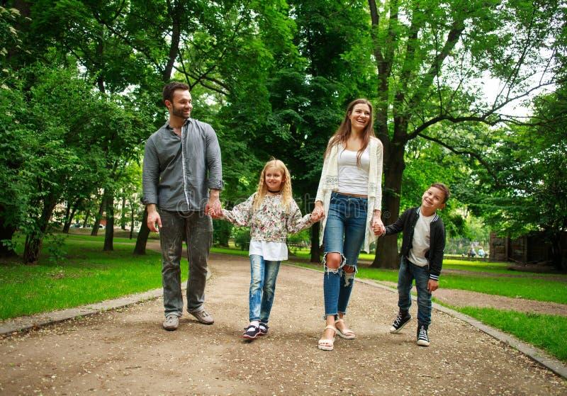 La familia feliz que camina llevando a cabo las manos en ciudad verde parquea fotografía de archivo