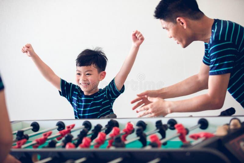 La familia feliz que juega al fútbol de la tabla para se relaja el día de fiesta en hogar fotos de archivo