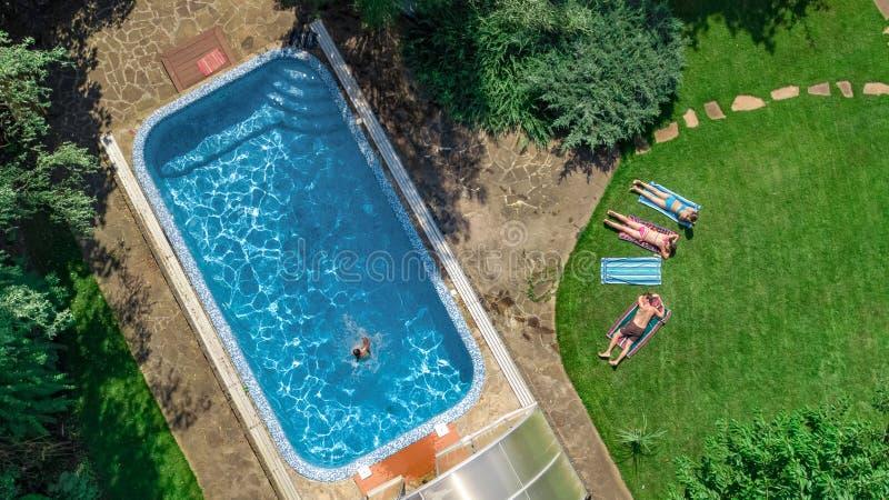 La familia feliz que se relaja por la piscina, la opinión aérea del abejón desde arriba de padres y los niños se divierten de vac imagen de archivo libre de regalías