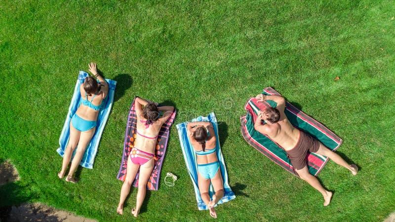 La familia feliz que se relaja por la piscina, la opinión aérea del abejón desde arriba de padres y los niños se divierten de vac imagenes de archivo