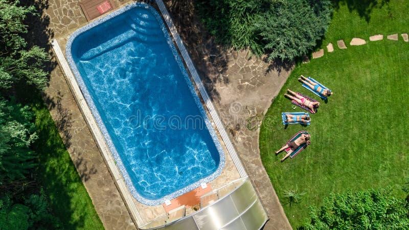 La familia feliz que se relaja por la piscina, la opinión aérea del abejón desde arriba de padres y los niños se divierten de vac foto de archivo