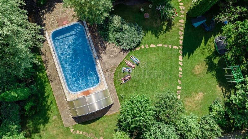 La familia feliz que se relaja por la piscina, la opinión aérea del abejón desde arriba de padres y los niños se divierten de vac fotografía de archivo libre de regalías