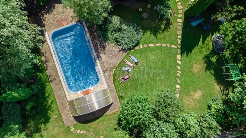 La familia feliz que se relaja por la piscina, la opinión aérea del abejón desde arriba de padres y los niños se divierten de vac imágenes de archivo libres de regalías