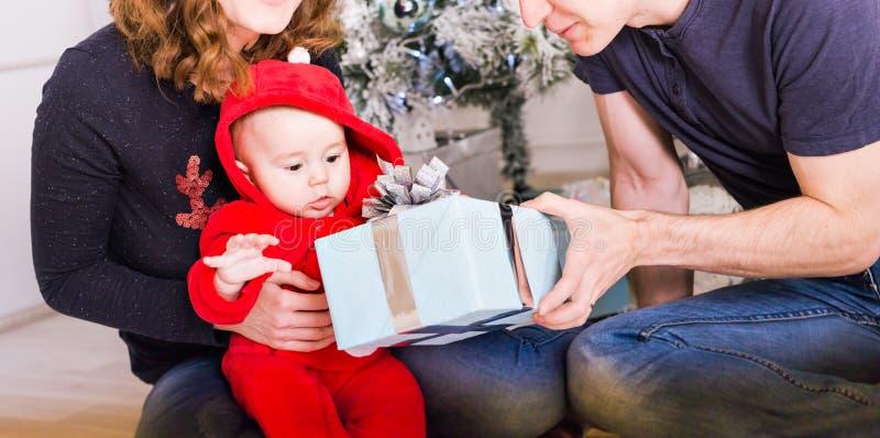 La familia feliz que sostiene los regalos de la Navidad acerca al árbol de Navidad Bebé, madre y padre divirtiéndose en casa imagenes de archivo