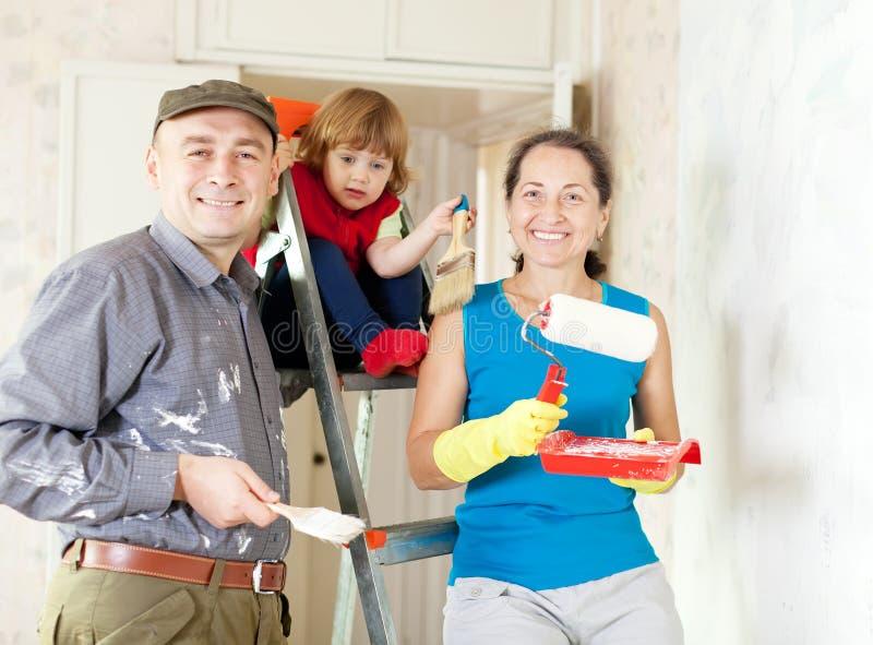 La familia feliz repara en casa imagenes de archivo