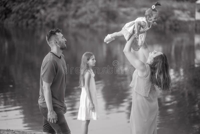 La familia feliz se divierte en un paseo y lanza para arriba a su pequeña hija al lado del lago imagenes de archivo