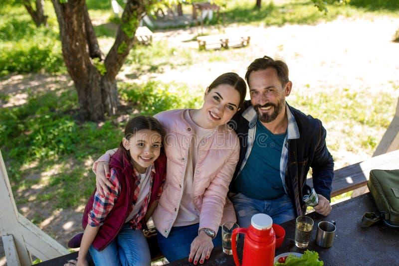 La familia feliz se está sentando en el banco en el Gazebo en parque y la sonrisa imágenes de archivo libres de regalías