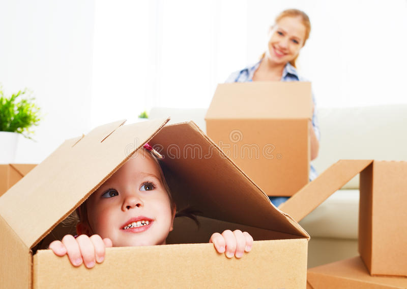 La familia feliz se traslada a un nuevo apartamento bebé feliz en un cardboa fotos de archivo