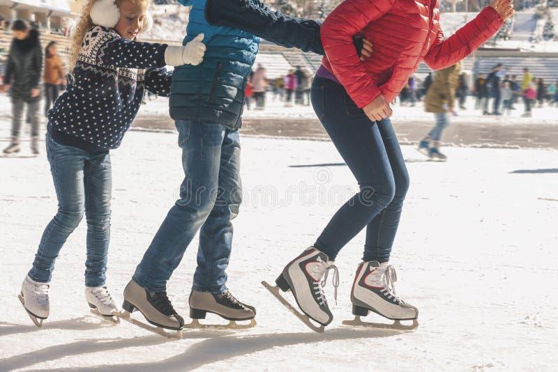 La familia feliz tiene actividad al aire libre, la Navidad, pista de patinaje al aire libre de hielo foto de archivo libre de regalías