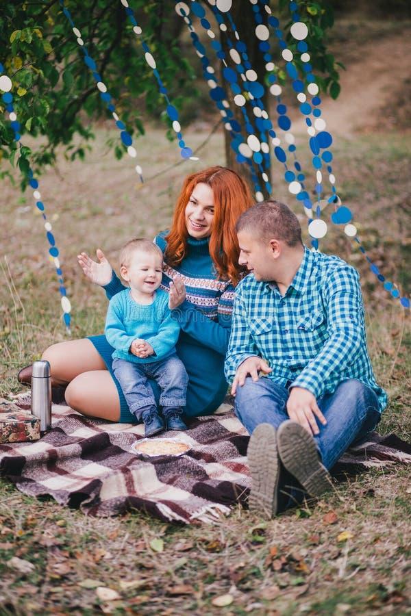 La familia feliz tiene fiesta de cumpleaños con las decoraciones azules en bosque fotografía de archivo