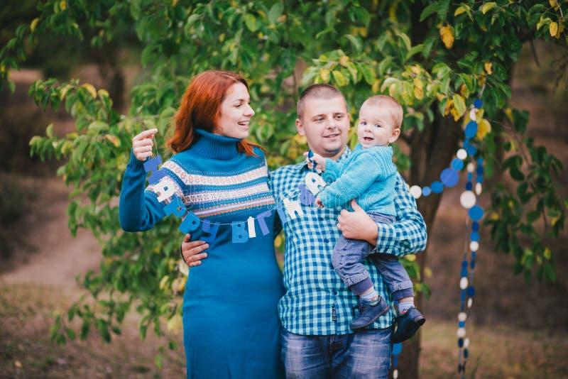 La familia feliz tiene fiesta de cumpleaños con las decoraciones azules en bosque imagen de archivo