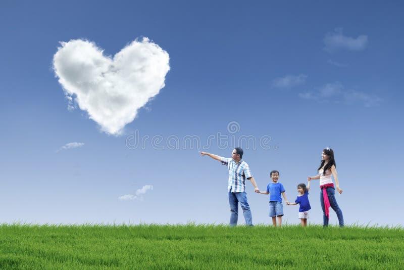 La familia feliz ve las nubes del corazón en el parque
