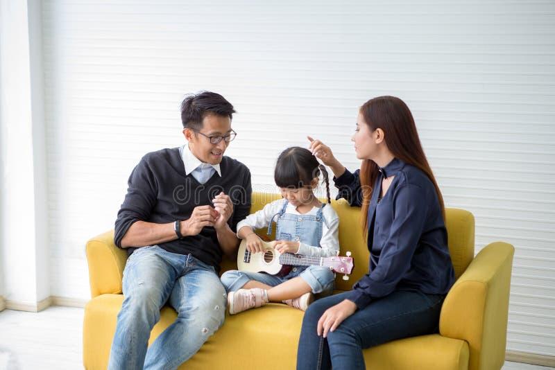 La familia feliz y los niños que juegan el ukelele que se sienta en el sofá, la madre y el padre animan así como hija imagen de archivo