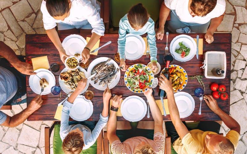 La familia grande cena con la comida cocinada fresca en el jardín abierto t imagenes de archivo