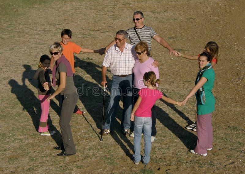 La familia grande en la diversión y el juego en la arena varan