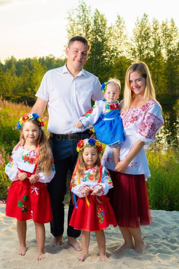 La familia grande en trajes ucranianos étnicos se sienta en el prado, el concepto de una familia grande imágenes de archivo libres de regalías