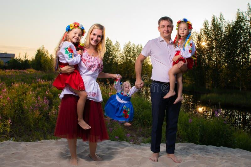 La familia grande en trajes ucranianos étnicos se sienta en el prado, el concepto de una familia grande imagen de archivo libre de regalías