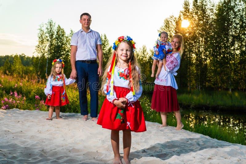 La familia grande en trajes ucranianos étnicos se sienta en el prado, el concepto de una familia grande imagenes de archivo