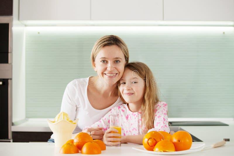 La familia hace el zumo de naranja en un juicer imagen de archivo libre de regalías