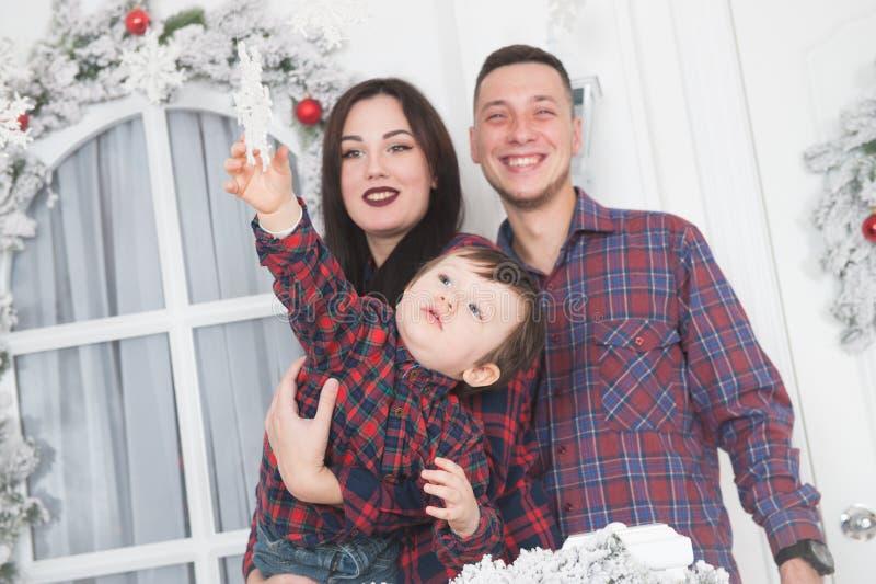 La familia hermosa joven con el niño pequeño quiere tomar el copo de nieve x fotos de archivo libres de regalías