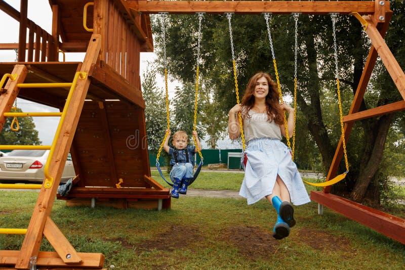 La familia hermosa se est? divirtiendo afuera Padres con los niños que montan en un oscilación La mamá está jugando con su poco h imagen de archivo