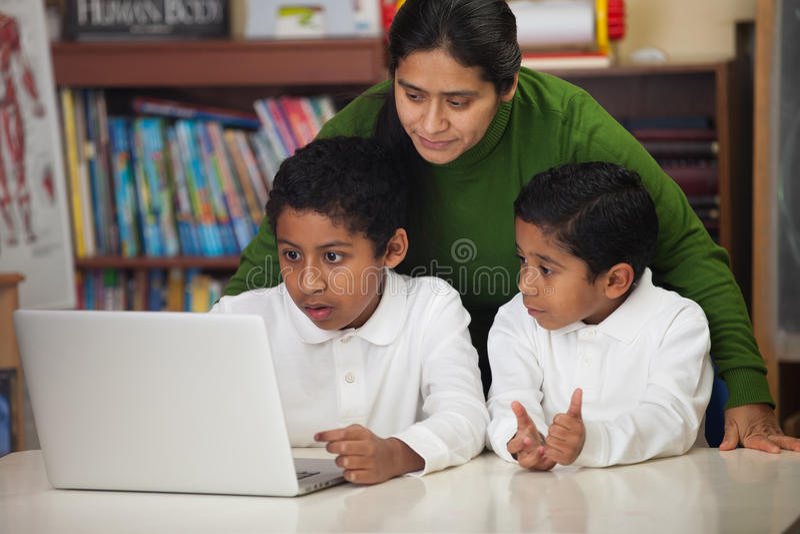 La familia hispánica con el ordenador portátil adentro enseña en casa el ambiente fotografía de archivo