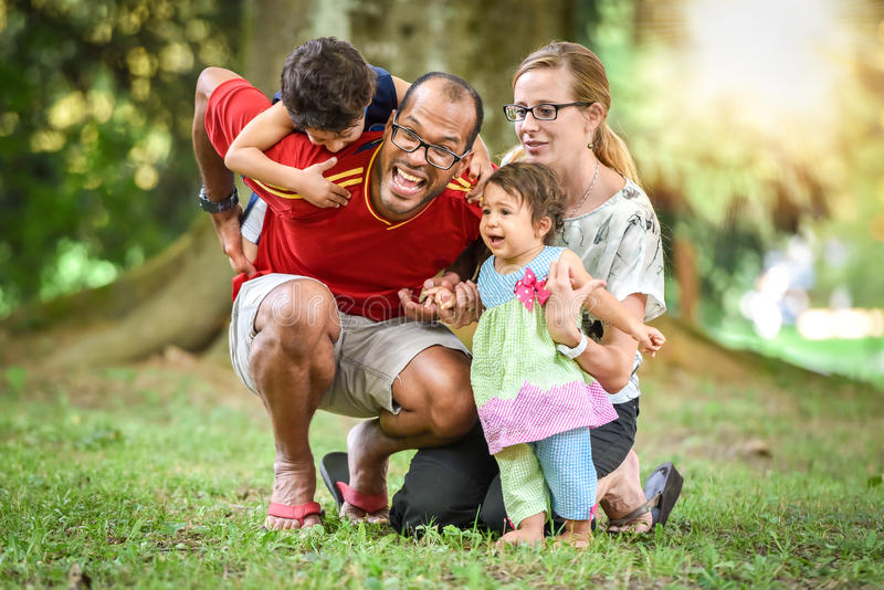 La familia interracial feliz está siendo activa un día en el parque imagen de archivo