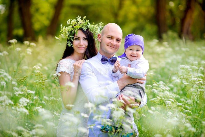 la familia joven camina con los niños en el parque hermoso en una puesta del sol, amistoso abrazo y la sonrisa, madre en la cabez fotografía de archivo libre de regalías